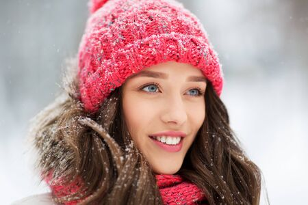 people, season and christmas concept - portrait of happy smiling teenage girl or young woman outdoors in winter park 写真素材