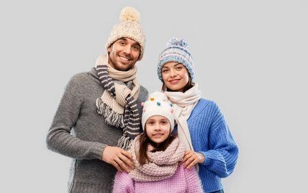 family, christmas and winter clothes concept - happy mother, father and little daughter in knitted hats and scarves over grey background