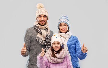 Familien-, Weihnachts- und Winterkleidungskonzept - glückliche Mutter, Vater und kleine Tochter in Strickmützen und Schals mit Daumen nach oben auf grauem Hintergrund Standard-Bild