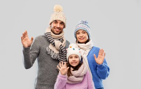 family, christmas and winter clothes concept - happy mother, father and little daughter in knitted hats and scarves waving hands over grey background