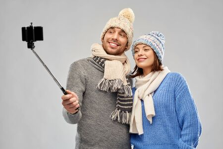 people, christmas and winter clothes concept - happy couple in knitted hats and scarves taking picture by smartphone on selfie stick over grey background
