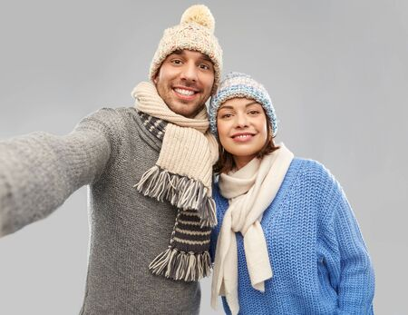 people, christmas and winter clothes concept - happy couple in knitted hats and scarves taking selfie over grey background