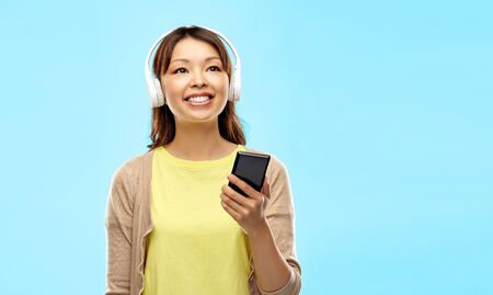 people, technology and audio equipment concept - happy asian young woman in headphones listening to music on smartphone over blue background