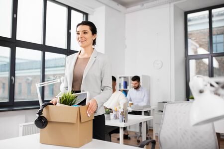 business, new job and corporate concept - happy smiling businesswoman with her personal stuff at office