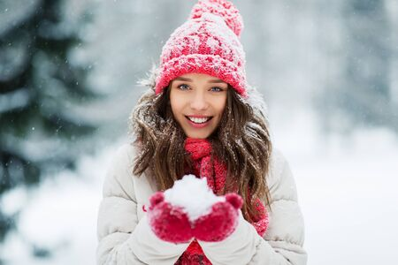 people, season and christmas concept - portrait of happy smiling teenage girl or young woman with snow in winter park