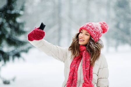 christmas, season and people concept - happy smiling teenage girl or young woman taking selfie by smartphone in winter park