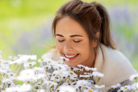 gardening and people concept - close up of happy young woman smelling chamomile flowers at summer garden 写真素材