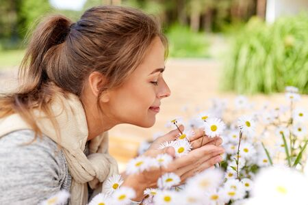 gardening and people concept - happy young woman smelling chamomile flowers at summer garden 写真素材 - 130120538