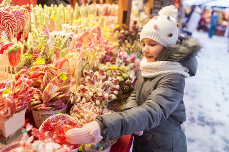 holidays, childhood and people concept - happy little girl choosing sweets at christmas market in winter evening