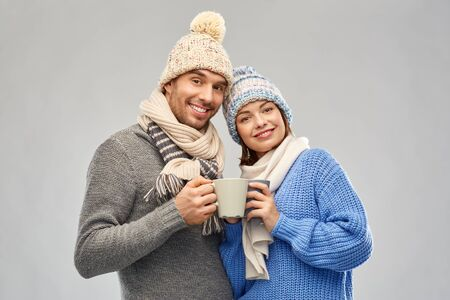 people, christmas and love concept - happy romantic couple in knitted hats and scarves with mugs over grey background