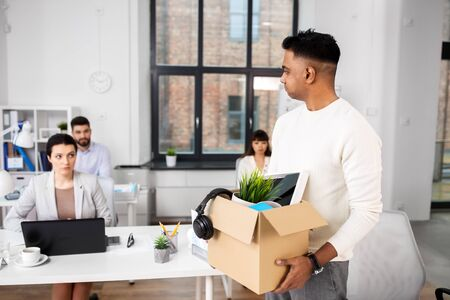 business, firing and job loss concept - sad fired indian male office worker with box of his personal stuff