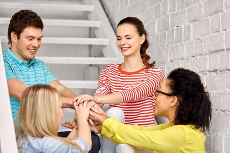 friendship and people concept - smiling teenage friends or students stacking hands hanging out on stairs