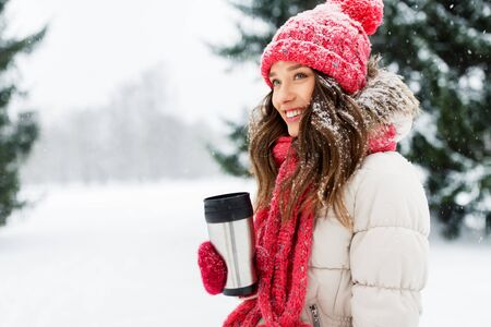 people, season, drinks and christmas concept - happy teenage girl or young woman with hot drink in tumbler outdoors in winter park Stock Photo