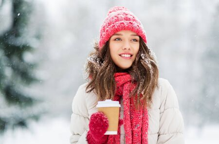 people, hot drinks and christmas concept - happy teenage girl or young woman drinking takeaway coffee outdoors in winter park