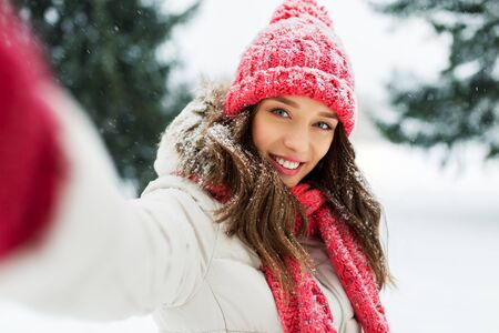 christmas, season and people concept - happy smiling woman taking selfie outdoors in winter park