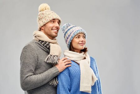 people, christmas and winter clothes concept - happy couple in knitted hats and scarves over grey background