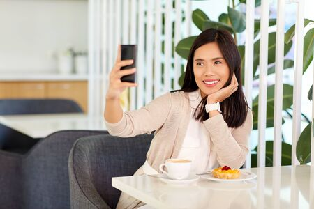technology and people concept - happy asian woman with cake and coffee taking selfie by smartphone at cafe