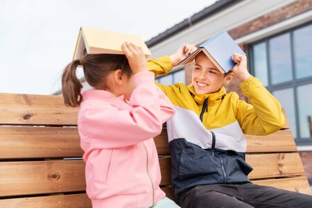 education, childhood and people concept - happy school children or brother and sister with books sitting on wooden street bench outdoors and having fun