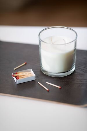 decoration, hygge and cosiness concept - white fragrance candle and matches on tray on table