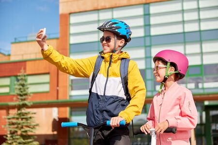 education, childhood and people concept - happy school children in helmets with backpacks and scooters taking selfie by smartphone outdoors Stockfoto