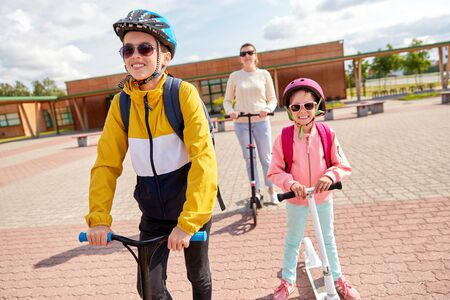 education, school and family concept - happy daughter, son and mother riding scooters outdoors