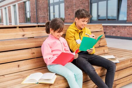 education, childhood and people concept - happy school children or brother and sister with notebooks and books sitting on wooden street bench outdoors Stockfoto