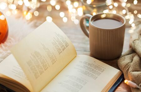 hygge and cozy home concept - book and cup of coffee or hot chocolate on table Standard-Bild