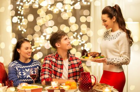 holidays and celebration concept - happy friends having christmas dinner at home
