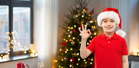 holidays and winter childhood concept - smiling little boy in santa helper hat showing ok hand sign over christmas tree at home background