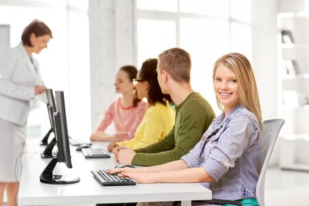 education, technology and learning concept - group of happy international high school students or classmates in computer class
