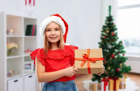 childhood and winter holidays concept - smiling girl in santa helper hat with gift box over christmas tree at home background