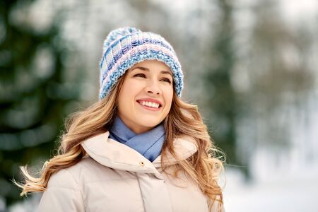 people, season and leisure concept - portrait of happy smiling woman outdoors in winter