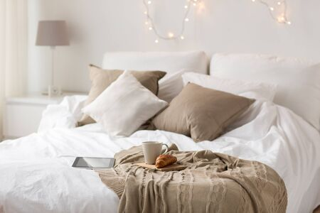 comfort, hygge and interior concept - tablet computer, cup of coffee and croissant on bed at cozy home