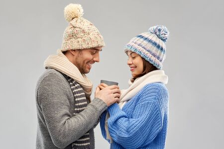 people, christmas and love concept - happy romantic couple in knitted hats and scarves holding one cup over grey background Stockfoto