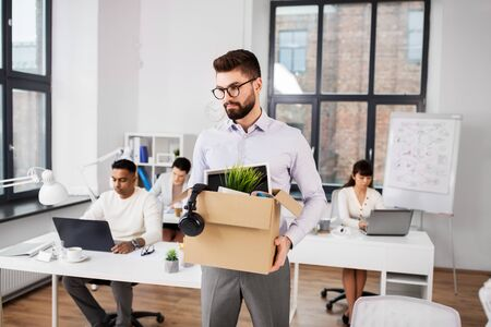 business, firing and job loss concept - sad fired male office worker with box of his personal stuff