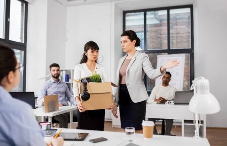 business, firing and job loss concept - executive and sad fired asian female office worker holding box of his personal stuff 写真素材