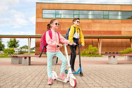 education, childhood and people concept - happy school children with backpacks and scooters outdoors Stock Photo