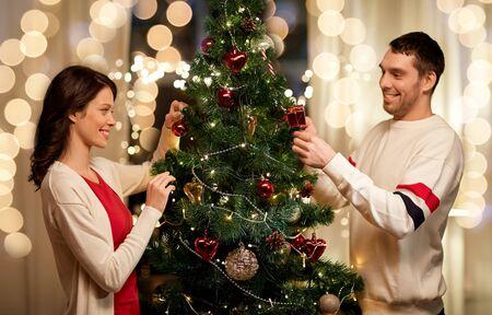 Vacaciones de invierno y concepto de personas - pareja feliz decorando el árbol de Navidad en casa Foto de archivo