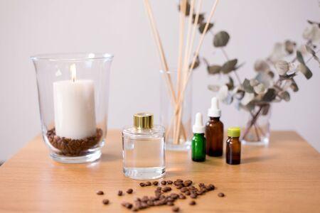 concept de décoration, de parfum d'intérieur et d'aromathérapie - diffuseur de roseaux aromatiques, bougie allumée et huile essentielle sur table à la maison