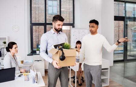 business, firing and job loss concept - executive seeing off sad fired male office worker holding box of his personal stuff