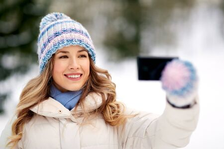 people, season and leisure concept - happy smiling woman taking selfie by smartphone in winter