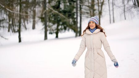 people, season and leisure concept - happy smiling woman outdoors in winter forest