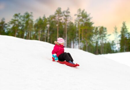 childhood, sledging and season concept - happy little girl sliding down snow hill on sled outdoors in winter over forest background