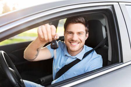 Transport-, Fahrzeug- und Eigentumskonzept - glücklicher lächelnder Mann oder Fahrer mit Schlüssel im Auto sitzend