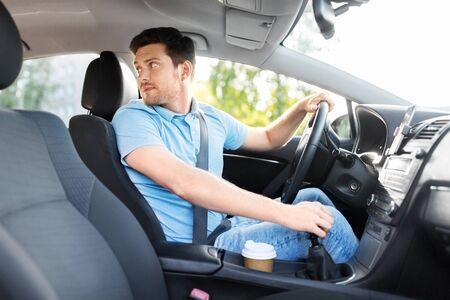 transport-, voertuig- en rijconcept - man of autobestuurder terugkijkend Stockfoto