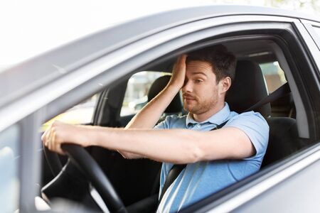 Transporte, vehículo y concepto de conducción: hombre cansado y soñoliento o conductor de automóvil frotándose los ojos Foto de archivo