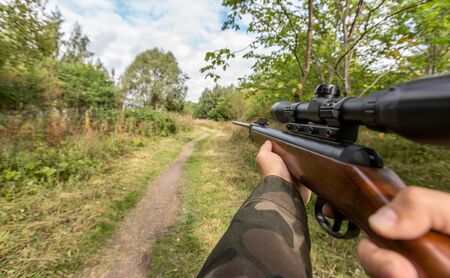 virtual reality game en geweld concept - POV van mannelijke handen schieten met luchtgeweer buitenshuis