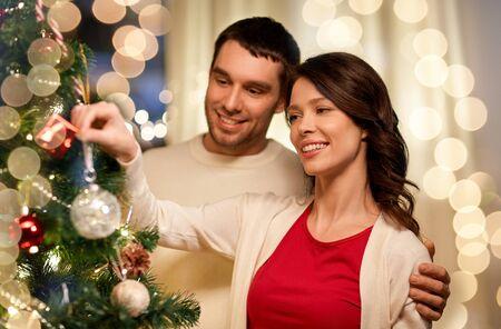 Vacaciones de invierno y concepto de personas - pareja feliz decorando el árbol de Navidad en casa