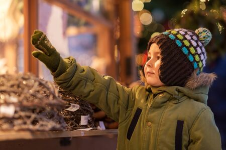 holidays, childhood and people concept - happy little boy at christmas market in winter evening Stock Photo