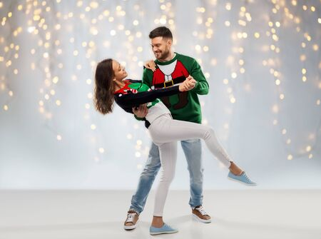christmas, people and holidays concept - happy couple dancing at ugly sweater party over festive lights background Stockfoto - 130228903